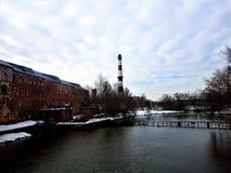 Il mattone ha abbandonato la pianta incustodita abbandonata con un tubo di pietra sul fiume, contro il cielo blu e le nuvole nell fotografia stock libera da diritti