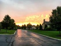 Il mattone rurale alloggia nella foresta e nei precedenti arancio del tramonto Fotografie Stock