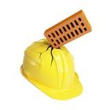 Il mattone si è arrestato attraverso un casco della costruzione Immagine Stock