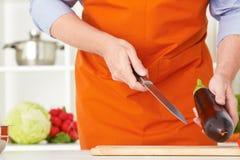 Il ` maturo s dell'uomo del primo piano passa le verdure di taglio su una superficie di lavoro in una cucina Immagini Stock Libere da Diritti