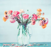 Il mazzo adorabile di bello ranunculus fiorisce in vaso di vetro sulla tavola al fondo blu-chiaro del turchese Fotografia Stock