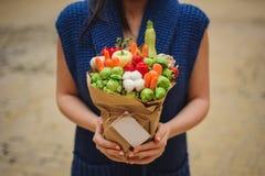 Il mazzo commestibile insolito originale della frutta e della verdura con la carta in mani della donna Immagine Stock Libera da Diritti
