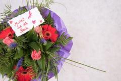 Il mazzo dei fiori con la carta mormora gli IST muore Beste in tedesco Fotografia Stock Libera da Diritti