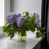 Il mazzo dei ramoscelli lilla in un barattolo trasparente sulla sedia bianca come decorazione dell'interno La ragazza si siede su fotografie stock