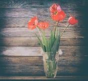 Il mazzo dei tulipani rossi dei fiori in un vaso di vetro su un granaio di legno del fondo si imbarca sul primo piano Fotografia Stock