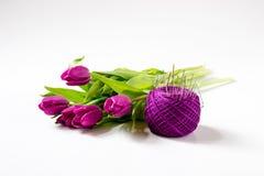 Il mazzo dei tulipani si trova dietro la palla di filato con gli aghi Immagine Stock