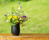 Il mazzo dei wildflowers e le bacche della fragola stanno sul terrazzo Fotografie Stock Libere da Diritti