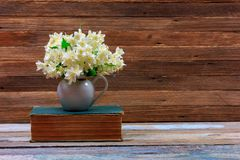 Il mazzo del gelsomino fiorisce in una brocca su un vecchio libro su una tavola su un retro fondo di legno marrone immagine stock libera da diritti