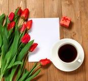 Il mazzo del tulipano è su fondo di legno, sulla tazza di caffè e sulla carta in bianco per testo fotografia stock libera da diritti