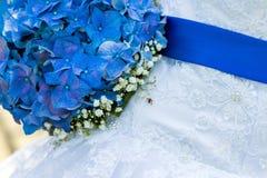 Il mazzo del vestito dalla sposa con un nastro blu Fotografie Stock
