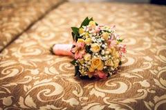 Il mazzo della bella sposa sul letto Fiori per la cerimonia nuziale Notte di cerimonia nuziale fotografia stock libera da diritti