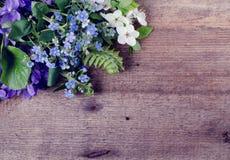 Il mazzo della primavera con le viole ed il nontiscordardime fiorisce su un fondo di legno con spazio per testo Immagine Stock Libera da Diritti