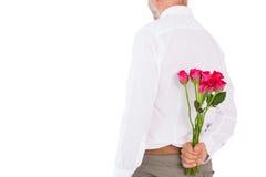Il mazzo della tenuta dell'uomo delle rose dietro appoggia Fotografia Stock