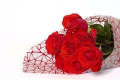 Il mazzo delle rose rosse si trova su un fondo bianco fotografia stock libera da diritti