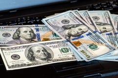 Il mazzo di banconote in dollari gettate su una tastiera del computer portatile ha caratterizzato il bokeh defocused immagini stock