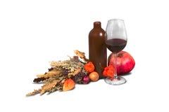 Il mazzo di campo eterogeneo diserba con la bottiglia, il bicchiere di vino e il pomeg Fotografia Stock