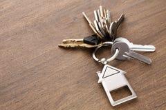 Il mazzo di chiavi con la casa ha modellato il keychain su legno bianco Fotografia Stock