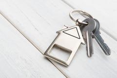 Il mazzo di chiavi con la casa ha modellato il keychain su legno bianco Immagini Stock Libere da Diritti
