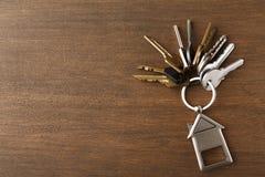 Il mazzo di chiavi con la casa ha modellato il keychain su legno bianco Immagine Stock