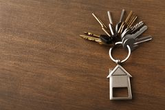 Il mazzo di chiavi con la casa ha modellato il keychain su legno bianco Immagini Stock