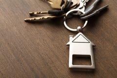Il mazzo di chiavi con la casa ha modellato il keychain su legno bianco Fotografia Stock Libera da Diritti