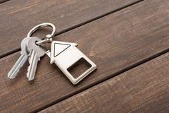 Il mazzo di chiavi con la casa ha modellato il keychain su legno marrone Fotografie Stock Libere da Diritti