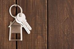 Il mazzo di chiavi con la casa ha modellato il keychain su legno marrone Fotografie Stock