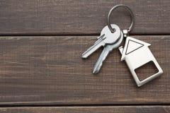 Il mazzo di chiavi con la casa ha modellato il keychain su legno marrone Immagine Stock Libera da Diritti