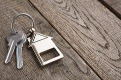 Il mazzo di chiavi con la casa ha modellato il keychain su legno rustico Fotografie Stock Libere da Diritti