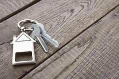 Il mazzo di chiavi con la casa ha modellato il keychain su legno rustico Fotografia Stock