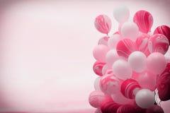 Il mazzo di colore rosa operato balloons il galleggiamento via dentro al cielo con il fondo d'annata del filtro Fotografie Stock Libere da Diritti