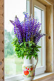 Il mazzo di lupino fiorisce in un vaso sul davanzale Immagini Stock
