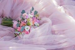 Il mazzo di nozze si trova sul vestito dal ` s della sposa fotografia stock