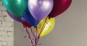 Il mazzo di palloni variopinti dell'elio sale su all'interno stock footage