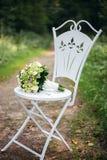 Il mazzo nuziale dei fiori bianchi e della pianta è su una sedia d'annata Fotografia Stock Libera da Diritti