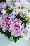 Il mazzo ricco di peonie rosa peonia e di rose di eustoma del lillà fiorisce in vaso di vetro su fondo bianco Stile rustico, natu Fotografie Stock Libere da Diritti