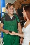 Il meccanico in camici verdi dà la bella ragazza in un whi fotografie stock libere da diritti