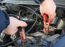 Il meccanico carica l'automobile di batteria Fotografia Stock