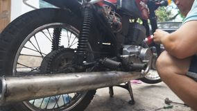 Il meccanico caucasico ripara il suo vecchio motociclo all'aperto Alto vicino del movimento lento video d archivio