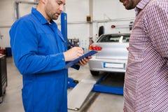 Il meccanico con la lavagna per appunti e l'uomo all'automobile comperano Fotografie Stock