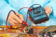 Il meccanico controlla il bordo elettronico con un multimetro Immagini Stock