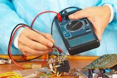 Il meccanico controlla l'hardware elettronico con un multimetro nell'officina di servizio Immagini Stock Libere da Diritti