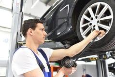 Il meccanico controlla la pressione d'aria di una gomma nel garage fotografie stock