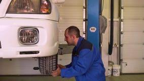 Il meccanico controlla lo stato dell'automobile spinge dentro il garage archivi video