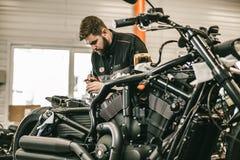 Il meccanico del motociclo che ripara l'elettronica mette in mostra la bici nera Fotografie Stock