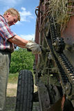 Il meccanico dell'attrezzatura dell'azienda agricola lubrifica il mecha della catena del rullo dell'olio per motori Fotografia Stock