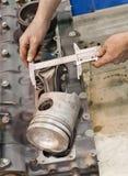 Il meccanico dettaglia la misura prima della riparazione del motore Immagine Stock