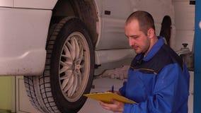 Il meccanico di automobile in abito blu ispeziona la gomma e scrive al primo piano della compressa archivi video