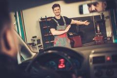 Il meccanico di automobile accoglie favorevolmente il nuovo cliente al suo servizio di riparazione automatica Immagine Stock Libera da Diritti