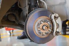 Il meccanico di automobile passa l'ispezione dell'ammortizzatore in vice a servizio di riparazione Stanza del garage Fotografia Stock